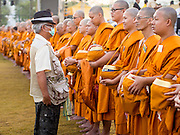 05 DECEMBER 2014 - BANGKOK, THAILAND:  A man talks to Buddhist monks lined up on Sanam Luang, the parade ground in front of the Grand Palace, for a Buddhist prayer service for Bhumibol Adulyadej, the King of Thailand. Thais marked the 87th birthday of the King Friday. The revered Monarch was scheduled to make a rare public appearance in the Grand Palace but cancelled at the last minute on the instructions of his doctors. He has been hospitalized in Siriraj Hospital, across the Chao Phraya River from the Palace, since early October.   PHOTO BY JACK KURTZ