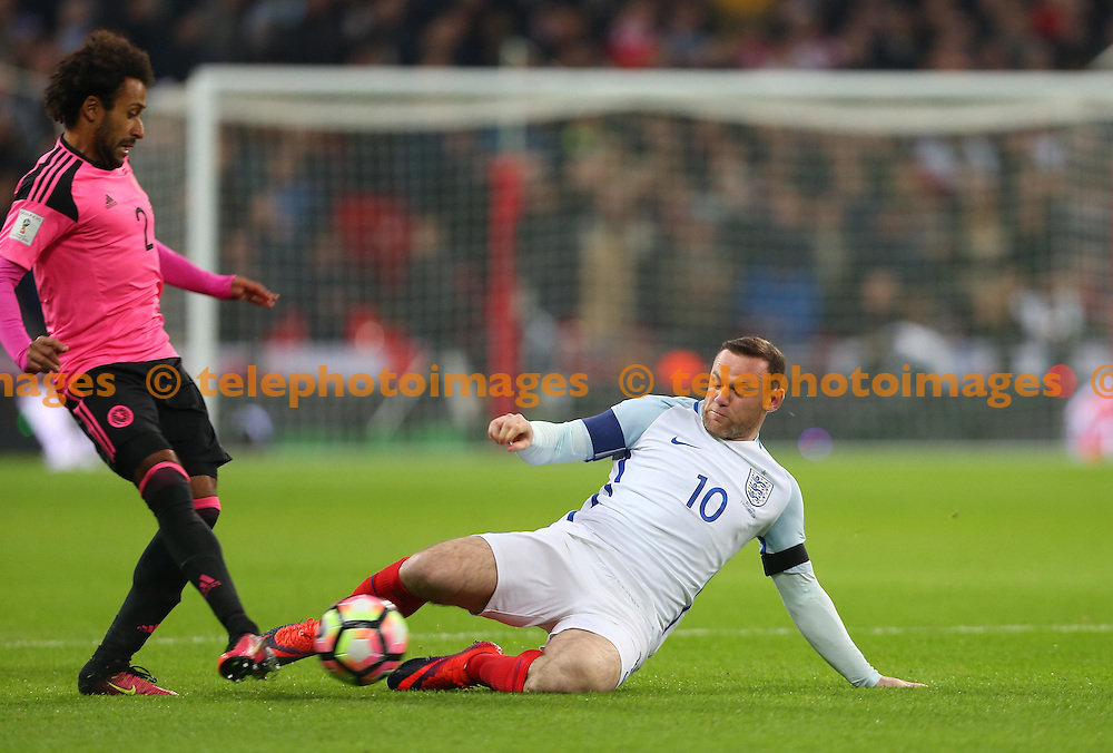 Wembley Stadium, London, UK.11th November 2016.  Wayne Rooney slides into tackle Ikechi Anya of Scotland during the FIFA World Cup Qualifier match between England and Scotland at Wembley Stadium in London. <br /> ©Telephoto Images / Alamy Live News