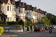 Suburban houses in evening sunshine and a passing moped on the corner of Deepdene and Ferndene Roads in the borough of Lambeth, and on 7th June 2021, in south London, England.