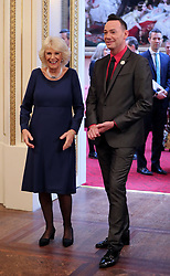Embargoed to 0001 Saturday December 23 The Duchess of Cornwall, President of the National Osteoporosis Society, is greeted by 'Strictly Come Dancing' judge Craig Revel Horwood as she arrives at Buckingham Palace in London to host a tea dance attended by 'Strictly Come Dancing' dancers and judges to highlight the benefits for older people of staying active.