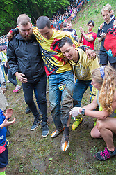 © Licensed to London News Pictures 26/05/2018, brockworth, Gloucester, UK. The annual cheese rolling race held at Coopers Hill, Brockworth outside Gloucester. Competitors race down the extremly steep slippery hill chasing a double Gloucester cheese, the winner of each race recieves the cheese as thier prize. Pictured here :  Local legend Chris Anderson  being atteneded to after injuring his leg in his second race where he won his  22nd and all time record breaking win - Photo Credit : Stephen Shepherd/LNP