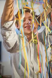 Teenager with paper streamers at birthday party