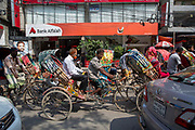Rickshaws, weaving between cars along a busy road past a branch of Bank Alfalah in the heat of the day on the 2nd of October 2018 in central Dhaka, Bangladesh.