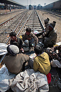 Youngsters wait for the next train to arrive at the train station in Jaipur.  Children, some who have run away from their families, find themselves living homeless on the train tracks waititng for the next train to arrive at the train station in Jaipur, India.  Once the train arrives they raid the train looking for plastic bottles that they can then sell.  Most will make about $1.50/day but spend most of it on glue which they are most addicted to.