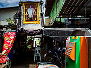 """21 JUNE 2017 - BANGKOK, THAILAND:  A payphone and a portrait of Bhumibol Adulyadej, the Late King of Thailand, in a community along the Chao Phraya River south of Krung Thon Bridge. This is one of the first parts of the riverbank that is scheduled to be redeveloped. The communities along the river don't know what's going to happen when the redevelopment starts. The Chao Phraya promenade is development project of parks, walkways and recreational areas on the Chao Phraya River between Pin Klao and Phra Nang Klao Bridges. The 14 kilometer long promenade will cost approximately 14 billion Baht (407 million US Dollars). The project involves the forced eviction of more than 200 communities of people who live along the river, a dozen riverfront  temples, several schools, and privately-owned piers on both sides of the Chao Phraya River. Construction is scheduled on the project is scheduled to start in early 2016. There has been very little public input on the planned redevelopment. The Thai government is also cracking down on homes built over the river, such homes are said to be in violation of the """"Navigation in Thai Waters Act."""" Owners face fines and the possibility that their homes will be torn down.                   PHOTO BY JACK KURTZ"""