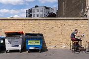 Alongside large rubbish bins, a  lunchtime diner sits on a stool in Spring sunshine at Smithfield Market in the City of London, the capitals financial district, on 27th May 2021, in London, England.
