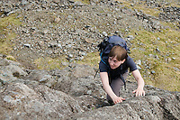 Female hiker climbs steep ridge to summit of Bla Bheinn, Black Cuillin mountains, Isle of Skye, Scotland
