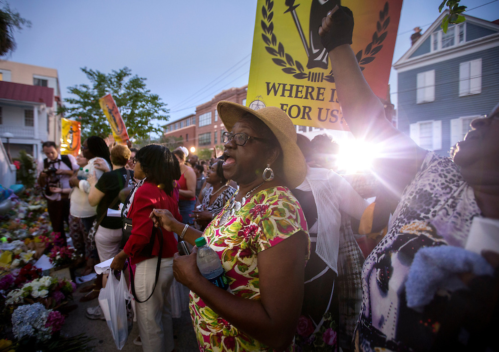 Carolyn Richardson, center, sings with a crowd of people gather outside the Emanuel AME Church, Friday, June 19, 2015 after a community prayer and healing vigil in Charleston, S.C. Thousands gathered at the College of Charleston TD Arena to bring the community together after nine people where shot to death at the church on Wednesday. (AP Photo/Stephen B. Morton)