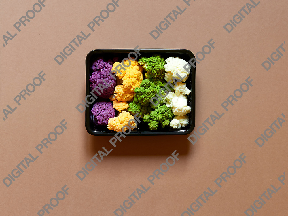 Set of seasonal and colorful cauliflower violet, yellow, green and white boxed in a plastic recipient  over a brown background