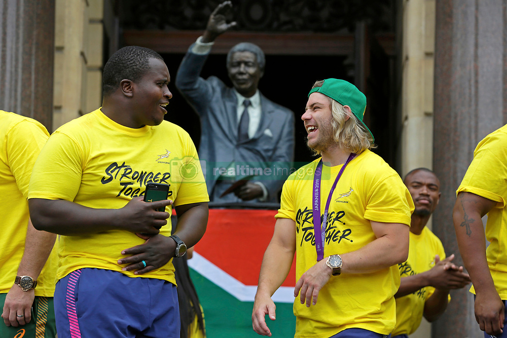 Monday 11th November 2019.<br /> City Hall, Grand Parade,<br /> And City Centre, Cape Town,<br /> Western Cape,<br /> South Africa.<br /> <br /> SPRINGBOKS CELEBRATE WINNING THE RUGBY WORLD CUP CHAMPIONSHIP IN 2019 WITH A COUNTRYWIDE VICTORY TOUR!<br /> <br /> SPRINGBOKS RUGBY WORLD CUP VICTORY TOUR CAPE TOWN!<br /> <br /> The Springboks take the stage outside the City Hall as they are cheered on by thousands of excited fans. On the right is South African Scrumhalf Faf de Klerk.<br /> <br /> The reigning Rugby World Cup Champions namely the South African Springbok Rugby Team, celebrates winning the Webb Ellis Cup during the International Rugby Football Board Rugby World Cup Championship held in Japan in 2019 with their Victory Tour that culminated in the final city tour taking place in Cape Town. Thousands of South African fans filled the streets of the city all trying their best to show their support for their beloved Springboks and to celebrate them winning the Rugby World Cup for the third time. South Africa previously won the Rugby World Cup in 1995, 2007 and now again in 2019. South African Springbok Captan Siya Kolisi took the opportunity to speak to the gathered crowd about how something like this brings unity and that we should live together as a nation that practices what is known as ubuntu. Ubuntu is a quality that includes the essential human virtues of compassion and humanity. This image taken in Cape Town on Monday 11th November 2019.<br /> <br /> This image is the property of Seven Bang Media Group (Pty) Ltd, hereinafter referred to as SBM.<br /> <br /> Picture By: SBM / Mark Wessels. (11/11/2019).<br /> +27 (0)61 547 2729<br /> mark@sevenbang.com<br /> www.sevnbang.com<br /> <br /> Copyright © SBM. All Rights Reserved.