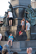 A father stands with children playing at the Adam Mickiewicz Monument in Rynek Glowny Square in Krakow, Poland (August 27, 2016)