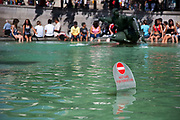Tourists and locals relax in the Summer sun at Trafalgar Square, central London. People come to cool off by the fountains, relax in deck chairs whilst visiting the National Gallery and other attractions. A sign warms people to not enter the water