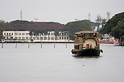 Thursday 14th August 2014: A trip boat built to look like a traditional backwater houseboat passes in front of the Brunton Boatyard Hotel.