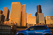 A young woman drives a stylish blue PT Cruiser on the elevated Alaskan Way Viaduct (slated to be replaced with a tunnel), skyscrapers rising behind her at sunset in downtown Seattle, Washington.