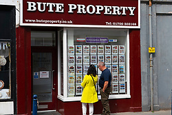 Two member so f public looking at houses for sale in wind ow of property estate agency in Rothesay , Isle of Bute, Scotland, UK