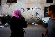"""Residents of Karaouine walk by grafitti that reads """"I am Tounsi"""". Enndha's victory will only last if they Islamist party is able to include Tunisia's many different groups and interests that all contributed to the revolution. This will change the country, but also Tunisia's version of Islam."""