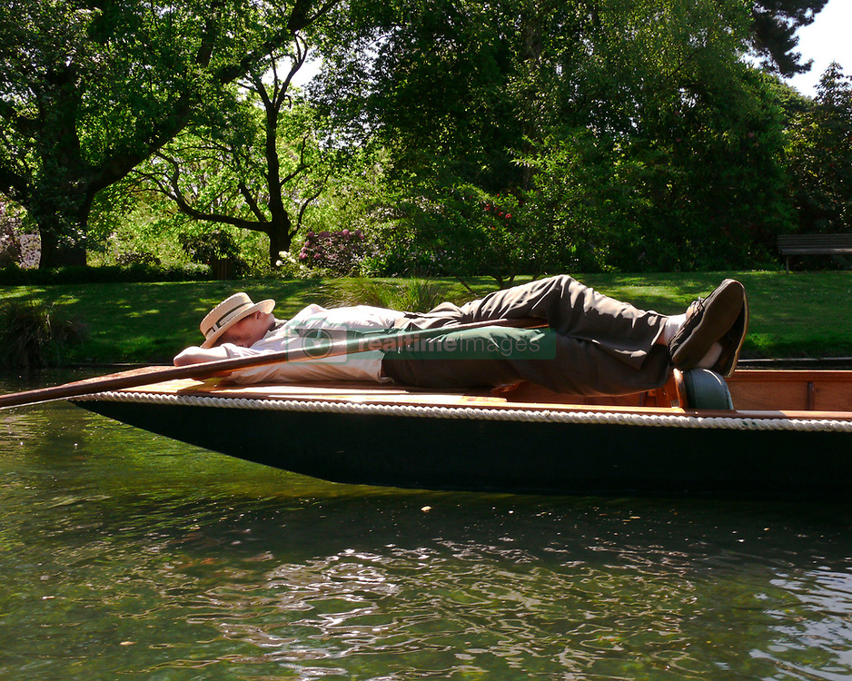Oct 30, 2008 - Christchurch, South Island, New Zealand - Edwardian-garbed punter, complete with straw boater hat, takes a nap on the stern of his flat-bottomed Cambridge-style punt on the banks of the Avon River. No visit to Christchurch is complete without the iconic experience of gliding down the Avon. The punter stands at the stern of the flat-bottomed boat propelled by a pole and performs a series of maneuvers requiring expertise, not simply pushing a punt around on the water.  (Credit Image: © Arnold Drapkin/ZUMA Press)