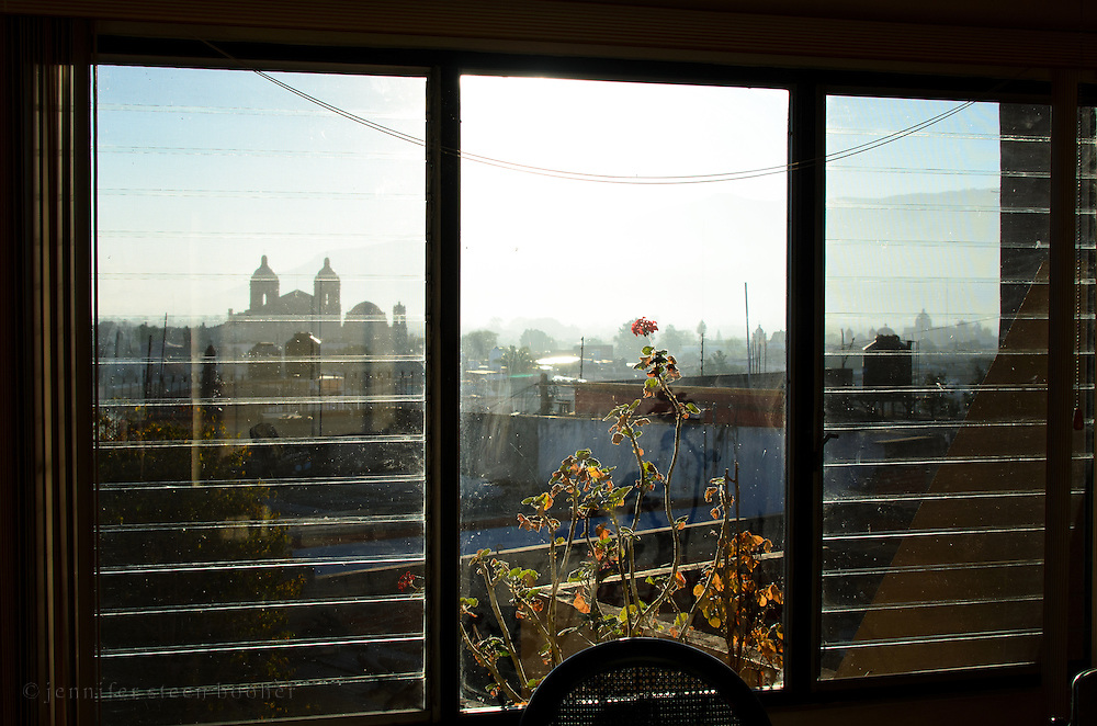 View through picture window of Oaxaca skyline including the church of Santo Domingo.