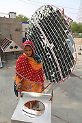 Moveable Parabolic mirrors heating an oven which can produce temperatures of up to 300 degrees centigrade relying only on the sun's rays, removing the need to use wood or other combustible materials..Barefoot College Tilonia, started by Bunker Roy in the 1970s. An organisation based upon creating economic self-empowerment and sustainable development initiatives, and self-sufficiency, for communities in the rural desert of Rajasthan, India. Energy autonomy with solar power capacitors, parabolic mirrors for cooking, solar powered water heating, and battery lanterns. Freshwater and irrigation through wells and desalination. A multitude of other economic initiatives run by grassroots Indian people, mainly women, where those who participate in, run the projects themselves. Many of them local lower castes, some physically handicapped, most with no paper qualifications, with support from others who gave up high flying money-making careers to be involved in working with poor rural communities. Mico-industries include solar lanterns, electric circuitry and lighting, crafts, textiles, children's toys, and sanitary towels. Also much emphasis on local and oral communications, radio, and puppetry. Now recognised internationally providing an educational resource most often directed towards communities of rural women worldwide.