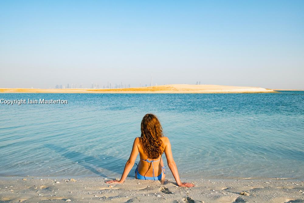 Woman on beach at The Island Lebanon beach resort on a man made island, part of The World off Dubai coast in  United Arab Emirates