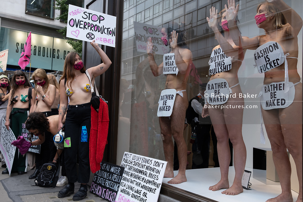 Supporters of environmental and Climate Change group Extinction Rebellion , protest against the ethics of the fashion industry by glueing their hands to the window of H&M on Oxford Street, on 9th September 2020, in London. XR say that the fashion industry produces around 10% of all humanity's carbon emissions, more than all international flights and maritime shipping combined and that over 800,000 tonnes of discarded textile waste annually in the UK.