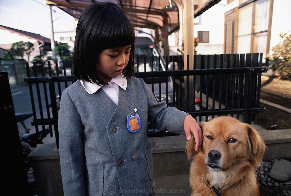 Maya Ukita and her dog before leaving home for her kindergarten class. Japan. Material World Project. The Ukita family lives in a 1421 square foot wooden frame house in a suburb northwest of Tokyo called Kodaira City.