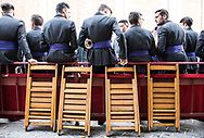 Musicians of a marching band wait to join the procession that will exit Seville Cathedral and walk back to its parish. Andalusia, Spain.