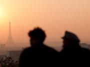 People watch sunset over the Eiffel Tower from Parc de Belleville, Paris, France