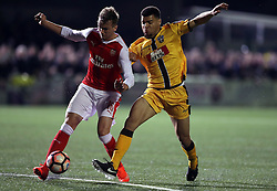 Arsenal's Rob Holding and Sutton's Maxime Biamou (right) battle for the ball during the Emirates FA Cup, Fifth Round match at Gander Green Lane, London.