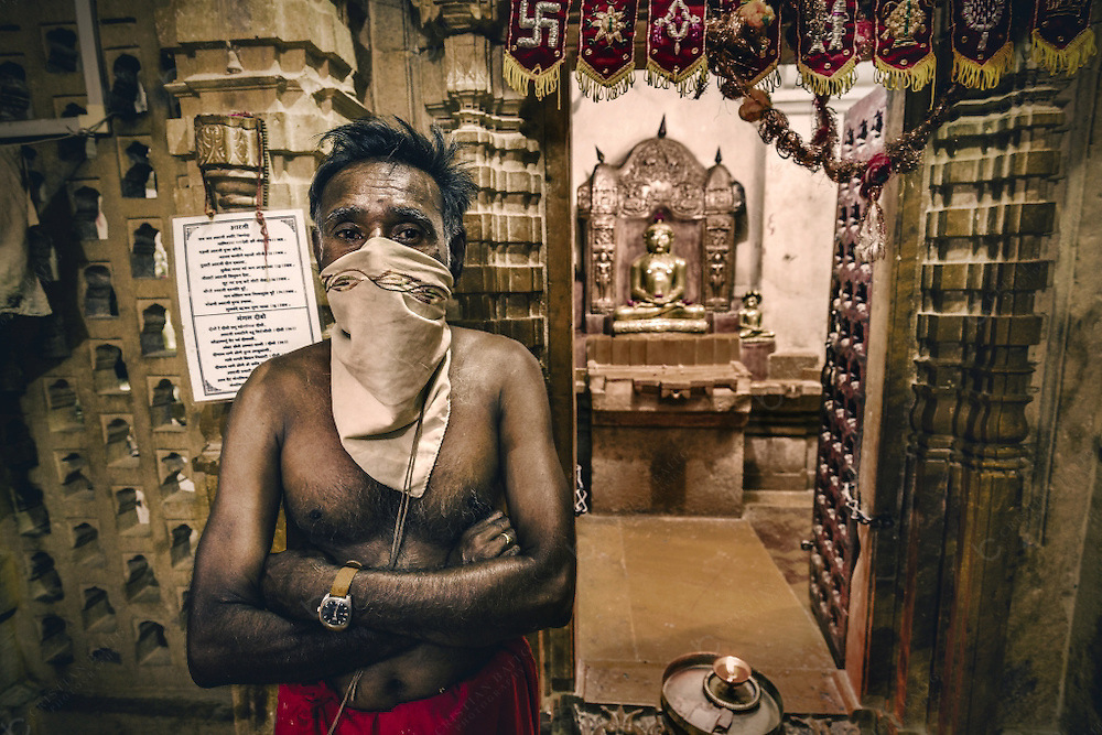 Jain priest inside the Jain temples complex in Jaisalmer Rajasthan India.  These buildings are built in the Dilwara style and are dedicated to Rikhabdevji and Shambhavdev Ji, the Jain hermits known as 'Tirthankars'. All of them have beautiful crafted carvings of yellow sandstones.Build from the 12th to the 15th century, this religious buildings are located within the Jaisalmer Fort.