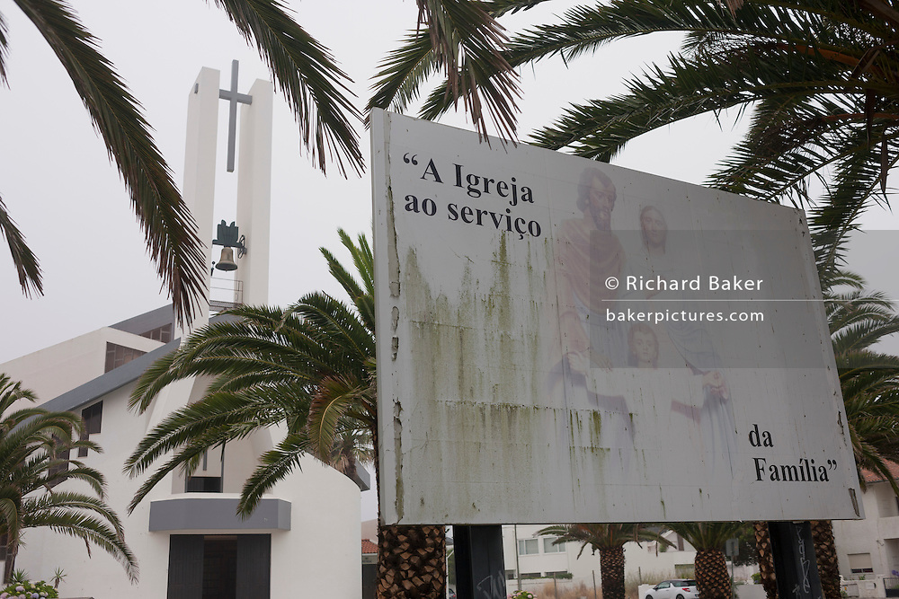 Religious lifestyle choices seen in a faded picture of Christian family morals, outside a Catholic church, on 18th July 2016, at Costa Novo, near Aveira, Portugal. Fading and suffering from green algae, the picture of the perfect family who attend Mass is seen in front of the tall cross and building exterior. There are an estimated nine million baptised Catholics in Portugal (84% of the population), in twenty dioceses, served by 2,789 priests. 19% of the national population attend mass and take the sacraments regularly. (Photo by Richard Baker / In Pictures via Getty Images)