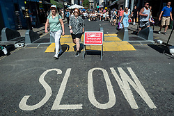 © Licensed to London News Pictures. 12/06/2021. LONDON, UK. People pass a Covid-19 temporary restrictions sign and a slow road sign in Soho.  Scientific advisers to the UK government have called for a delay to the complete lifting of coronavirus lockdown restrictions on 21 June, possibly by four weeks, to allow scientists to assess the link between rising numbers of Covid-19 cases (mainly the newly identified Delta variant) and hospital admissions.  Photo credit: Stephen Chung/LNP
