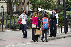 © Licensed to London News Pictures. 30/07/2016. LONDON, UK. A police officer speaks to local residents at the Police cordon outside Bethnal Green tube station on Cambridge Heath Road, where a man in his 30's was stabbed and later died in hospital last night.  Photo credit: Vickie Flores/LNP