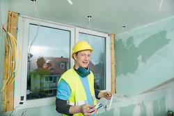 Portrait of construction worker with safety helmet and ear defenders holding a  measuring tape