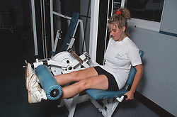 Woman working out in gymnasium using machine,