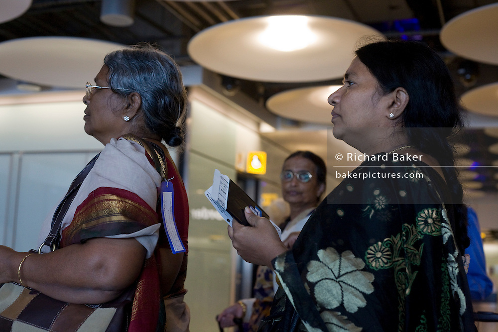 Airline passengers from India await transit instructions in line at Heathrow Airport's Terminal 5 arrivals concourse.