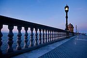 Street lamps line the promenade along the seawall at dusk in Cadiz, Spain