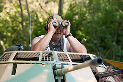 A reenactor portraying a German paratrooper (Fallschirmjäger) from the 1st fallschirmjäger Division, 3rd fallschirmjäger Regiment on Gothic line Italy dressed in tropical uniform.He is sitting with Binoculars (field glasses) in the turret of an SdKfz 222 light armored car which were used as reconnaissance vehicles. <br /> At the Hull Veterans Weekend <br /> 26 July 2014<br /> Copyright Paul David Drabble<br /> www.pauldaviddrabble.co.uk
