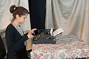 Young secretary in her 20s, working on an old style typewriter on an old style floral tablecloth retro reproduction