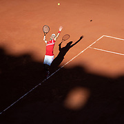 PARIS, FRANCE June 13.   Novak Djokovic of Serbia serving as the early evening shadows creep across the court during his match against Stefanos Tsitsipas of Greece on Court Philippe-Chatrier during the Men's Singles Final at the 2021 French Open Tennis Tournament at Roland Garros on June 13th 2021 in Paris, France. (Photo by Tim Clayton/Corbis via Getty Images)