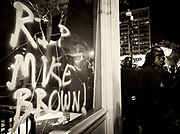 Police guard Oakland storefronts from being further vandalized.