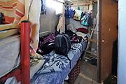Spanje, El Ejido, 8-11-2019 Een groep Marokkaanse jongeren woont in een klein huisje, voorheen boeren arbeiderswoningen. Hier verblijven 13 man (!). Enkele slapen op schappen aan de muur. Ze zijn zeer terughouden om op de foto te gaan en willen geen namen noemen want ze hebben het idee dat europese journalisten en fotografen alleen maar aan hun ellende willen verdienen. Het is echter belangrijk het verhaal van de uitbuiting van vooral Afrkaanse migranten te laten zien .  Pas na 3 jaar kun je een werkvergunning aanvragen, soms via een werkgever die daar geld voor wil terugzien . Sommigen hebben die, anderen zijn tot die tijd illegaale, illegale immigranten .In dit deel van Andalucie worden veel groenten en fruit verbouwd die hun weg vinden via de export naar o.a. Nederland . Het wordt de zee van plastic genoemd omdat de kassen opgebouwd zijn van houten of metalen palen bedekt met zwaar plastic. In de kassen werken voornamelijk migranten uit Afrika, en arbeidsmigranten uit Oost-Europa die een laag loon uitbetaald krijgen, tussen de 30 en 40 euro per 8 urige dag, werkdag, afhankelijk van de werkgever. Er wordt door de tuinders en transportbedrijven goed verdiend maar de boeren vinden dat ze teveel negatieve aandacht krijgen in de media van noord-europa. De migranten zijn zich ervan bewust dat ze van veel de schuld krijgen terwijl ze toch het werk doen wat de Spanjaarden niet willen... Foto: Flip Franssen