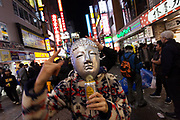 Young Japanese men wearing Buddha masks enjoy the Halloween celebrations in Shibuya. Saturday October 28th 2017