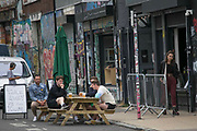 London, UK. 04/07/2020 People enjoy drinks in Hackney Wick, east London, as pubs reopen following the easing of coronavirus lockdown restrictions across England. The easing of restrictions, which were imposed on March 23, allows businesses including pubs restaurants and hair salons, to reopen to members of the public with measures in place to prevent the spread of the coronavirus.  Photo credit: Marcin Nowak/VXP