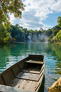 A wooden boat tied to shore at Kravice, a waterfall on the Trebižat River in Bosnia and Herzegovina. It is located about 40 kilometers south of Mostar.