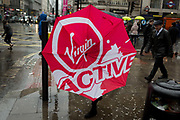 A lady carrying a Virgin Active brolly which has caught in the wind as Storm Georgina swept across parts of Britain and in central London, lunchtime office workers were caught out by torrential rain and high winds, on 24th January 2018, in London, England. Pedestrians resorted to leaping across deep puddles at the junction of New Oxford Street and Kingsway at Holborn, the result of overflowing drains. Fifth in a sequence of eight photos.