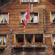 Traditional wooden swiss house with flag in Alps