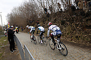 Belgium, March 31 2013: On the second pass over the Oude-Kwaremont, a small group of riders led the race. Mirko Selvaggi, VACANSOLEIL-DCM, looks back at Michal Kwiatkowski, OMEGA PHARMA-QUICK STEP, and Andre Greipel, LOTTO-BELISOL, during the elite men's edition of the Ronde van Vlaandaren 2013 cycle race. Copyright 2013 Peter Horrell.
