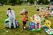"""19 JULY 2020 - DES MOINES, IOWA: A child looks at toys during """"A Celebration of Black Motherhood"""" in Des Moines Sunday. The event was organized by the Supply Hive and Black Lives Matter. Items were donated by members of the community and redistributed to at risk families. They distributed diapers, sanitary products, clothes, books, and toys. They had enough material to help 200 families.        PHOTO BY JACK KURTZ"""