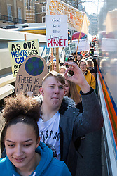 London, UK. 15th February, 2019. Students pass alongside a police vehicle as they block Whitehall during the YouthStrike4Climate for Climate Day which was attended by thousands of young people. Strike events involving schools all over the UK were organised by UK Student Climate Network and the UK Youth Climate Coalition to demand that the Government declare a climate emergency and take positive steps to address the climate crisis, including highlighting the issue as part of the school curriculum, as well as lowering the voting age to 16.